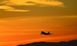 airplane in the air at sunset